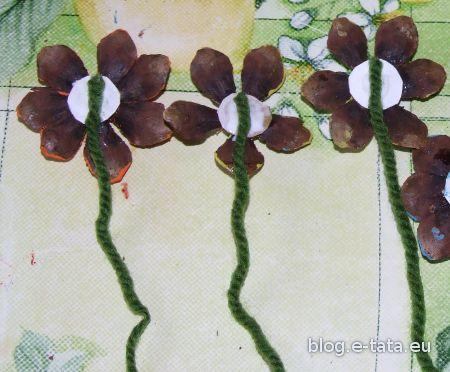 Kwiatki sklejone z płatków szyszek, z przyklejoną łodygą z wełny